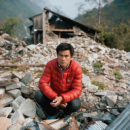 Chandra Ghale crouches on rubble