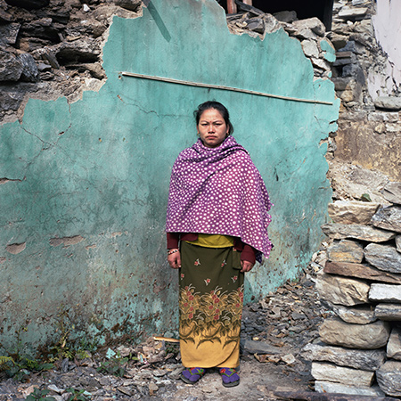 Laxmi Gurung stands in front of a blue wall