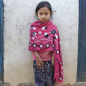 A young girl stands in between two doorways in Nepal