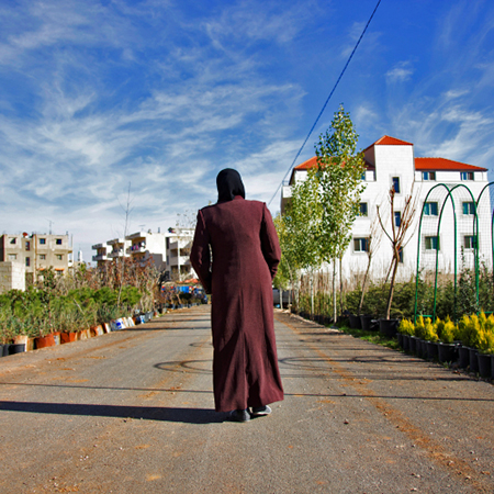 The back of a Syrian woman walking down a path