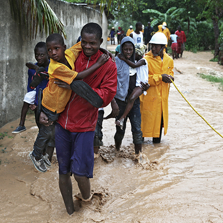 A group of people wading through floodwaters in Haiti after Hurricane Matthew hit