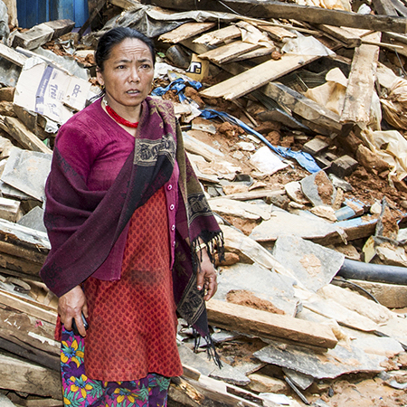 On the main road through the village of Sindupalchowk, Nepal, a woman stands by the building that was once her home after the 2015 earthquake.