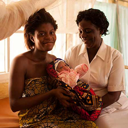 March 2015, Nigeria: Onuchukwu Okoye has just given birth; seen here with staff nurse and midwife Dorothy Ukowfu.