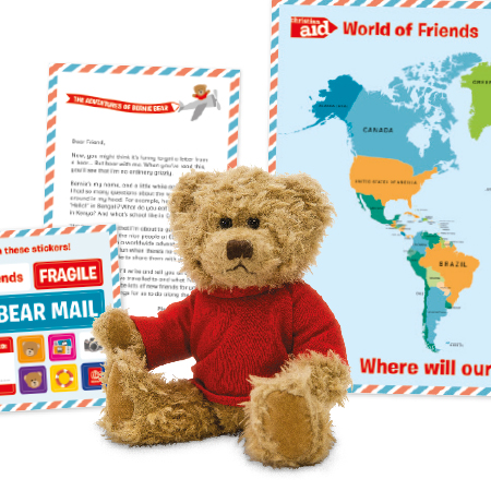 Bernie Bear soft toy sitting in front of the World of Friends welcome pack