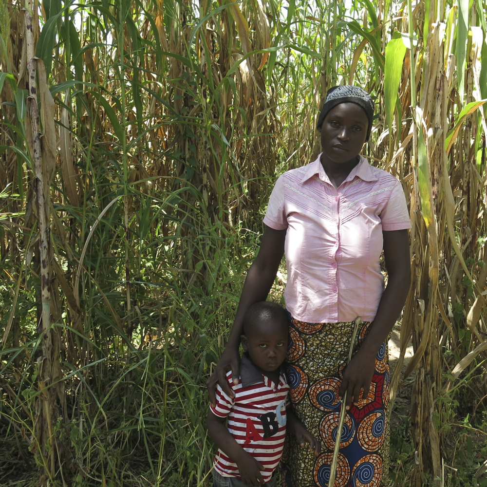 Patricia and her three-year-old son stand in front of tall grass