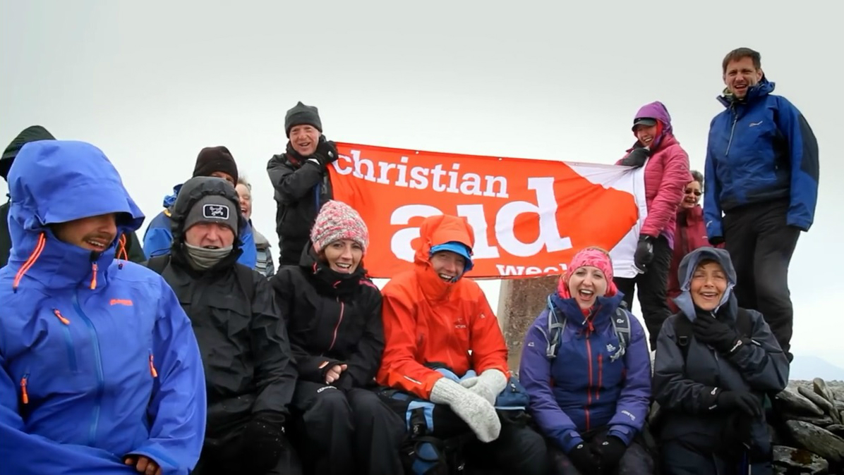 Fundraisers on a mountain with Christian Aid Week banner
