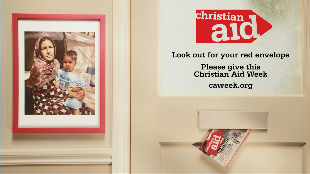 A red Christian Aid envelope arriving through a letterbox