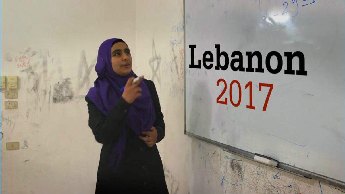A teacher standing in front of a whiteboard at a school in Lebanon