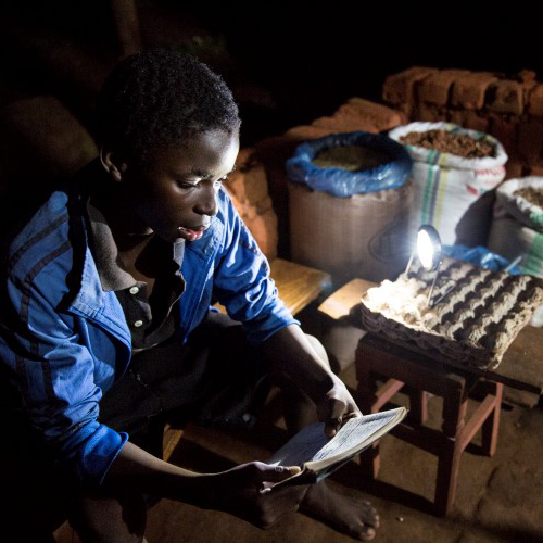 A child in Malawi reads in the dark by solar powered light