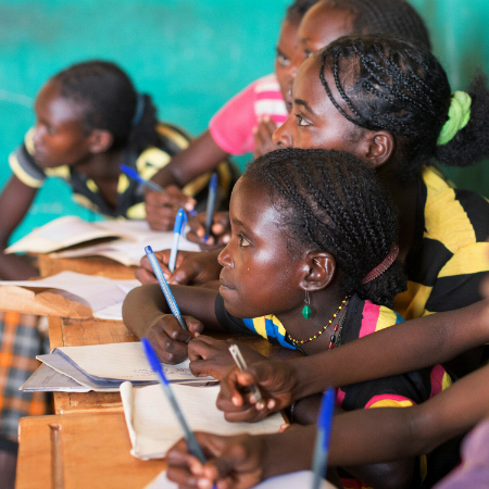 A group of children writing notes at school in Ethiopia