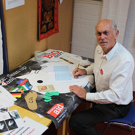 John Griffith, a volunteer teacher, sits at a desk using Christian Aid resources