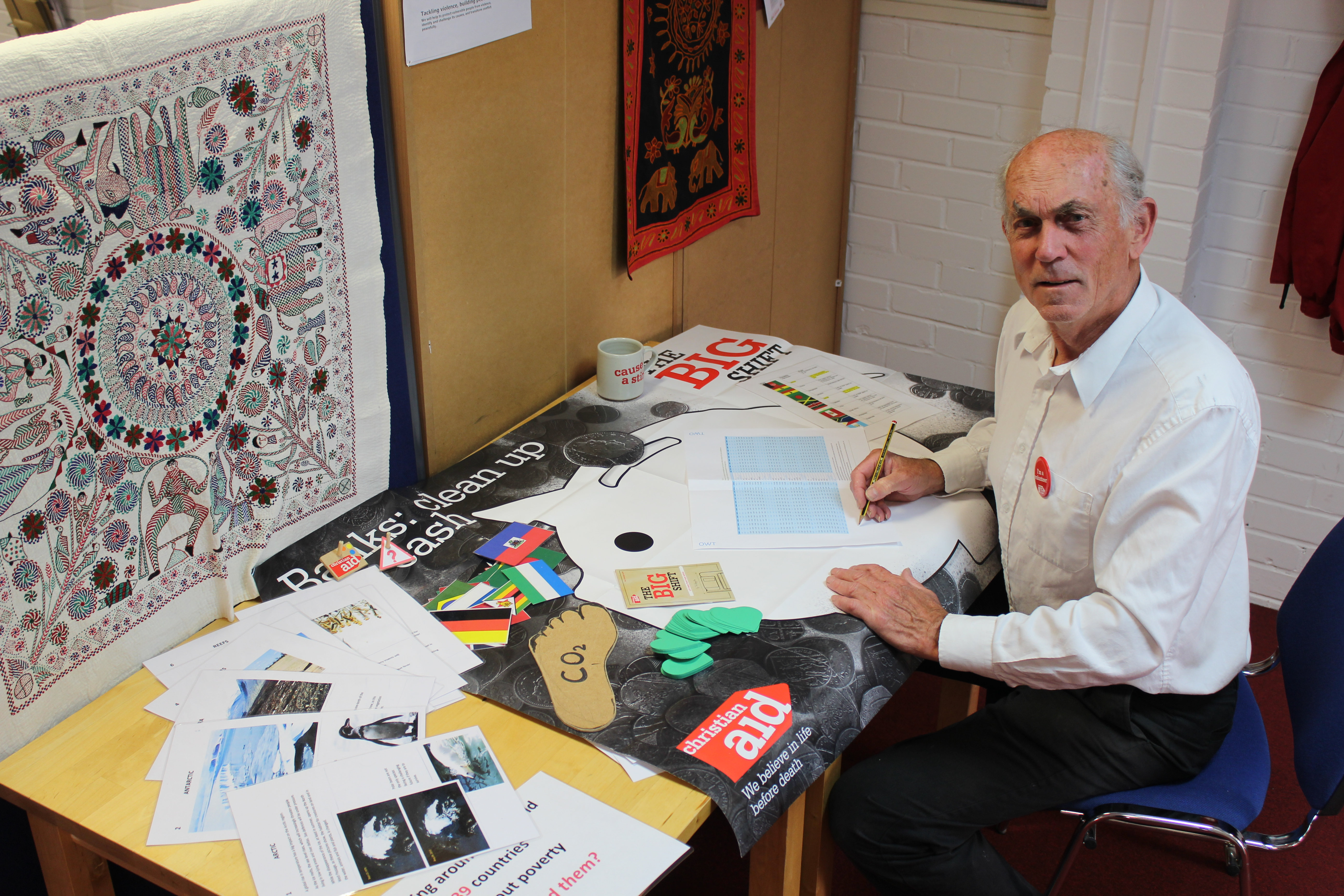 John Griffith, a volunteer teacher sits at a desk