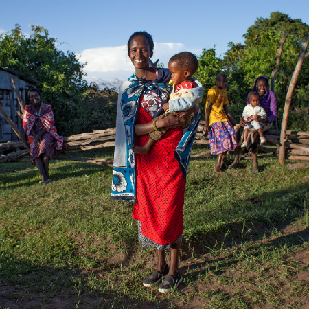 Joyce Katato stands in her Masai village holding her child