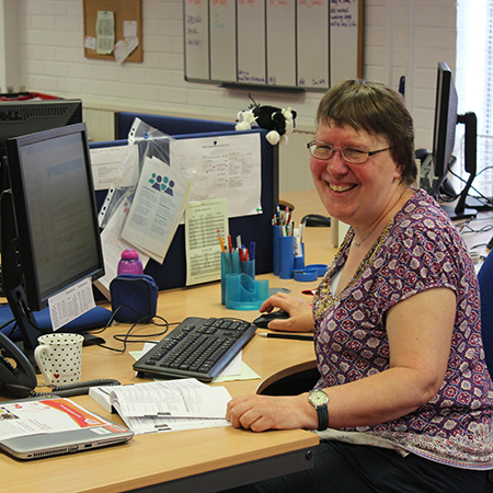 Liz Gwynne, an office volunteer, sits at a desk in a Christian Aid office