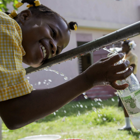 Young girl in school uniform fills up a bottle of water from a tap in Haiti