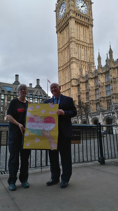 Anna Jane Evans and Hywel Williams hold up a placard at Westminster