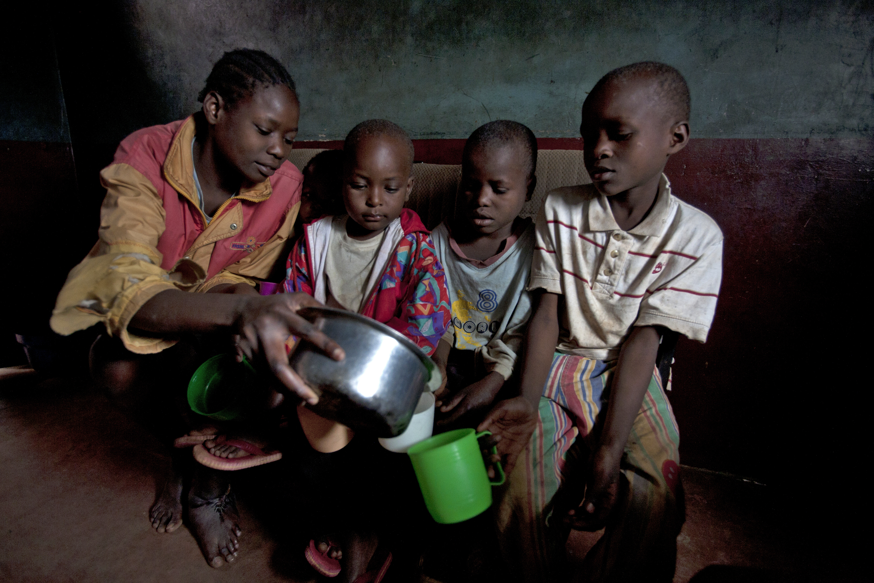 Jackline Adhiambo sit with three of her siblings pouring water into their cups