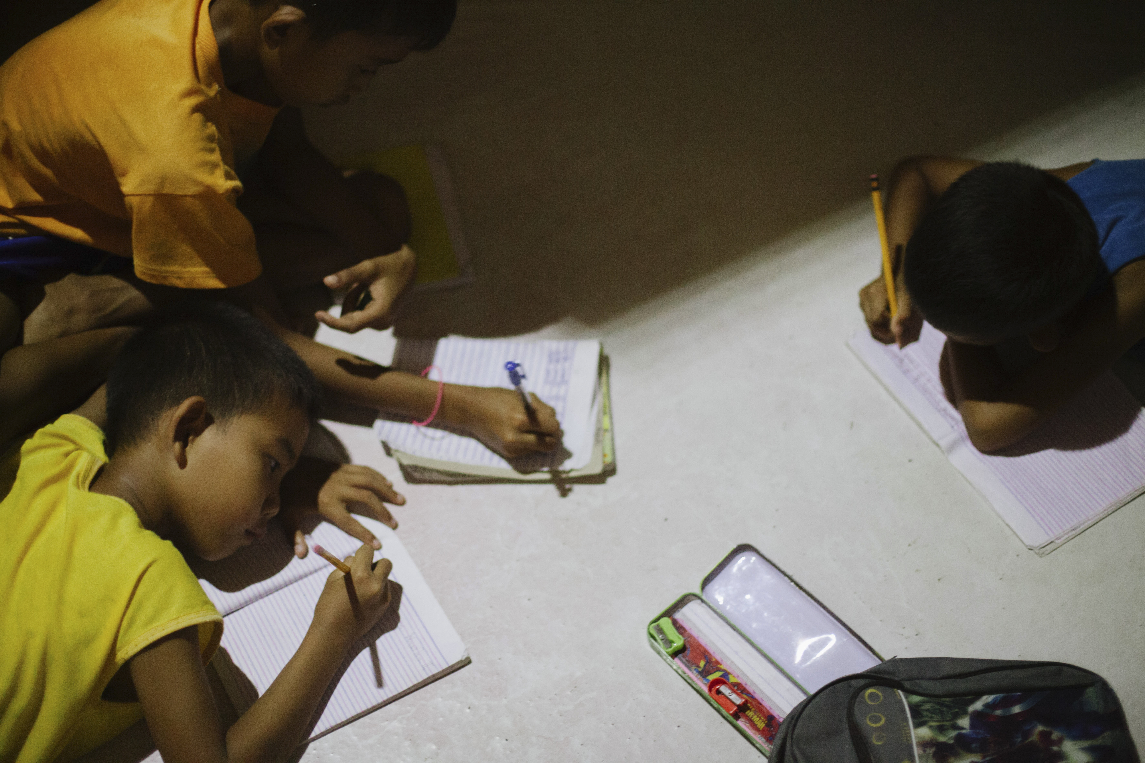 Sussett Enolva's children do their homework around the kitchen table