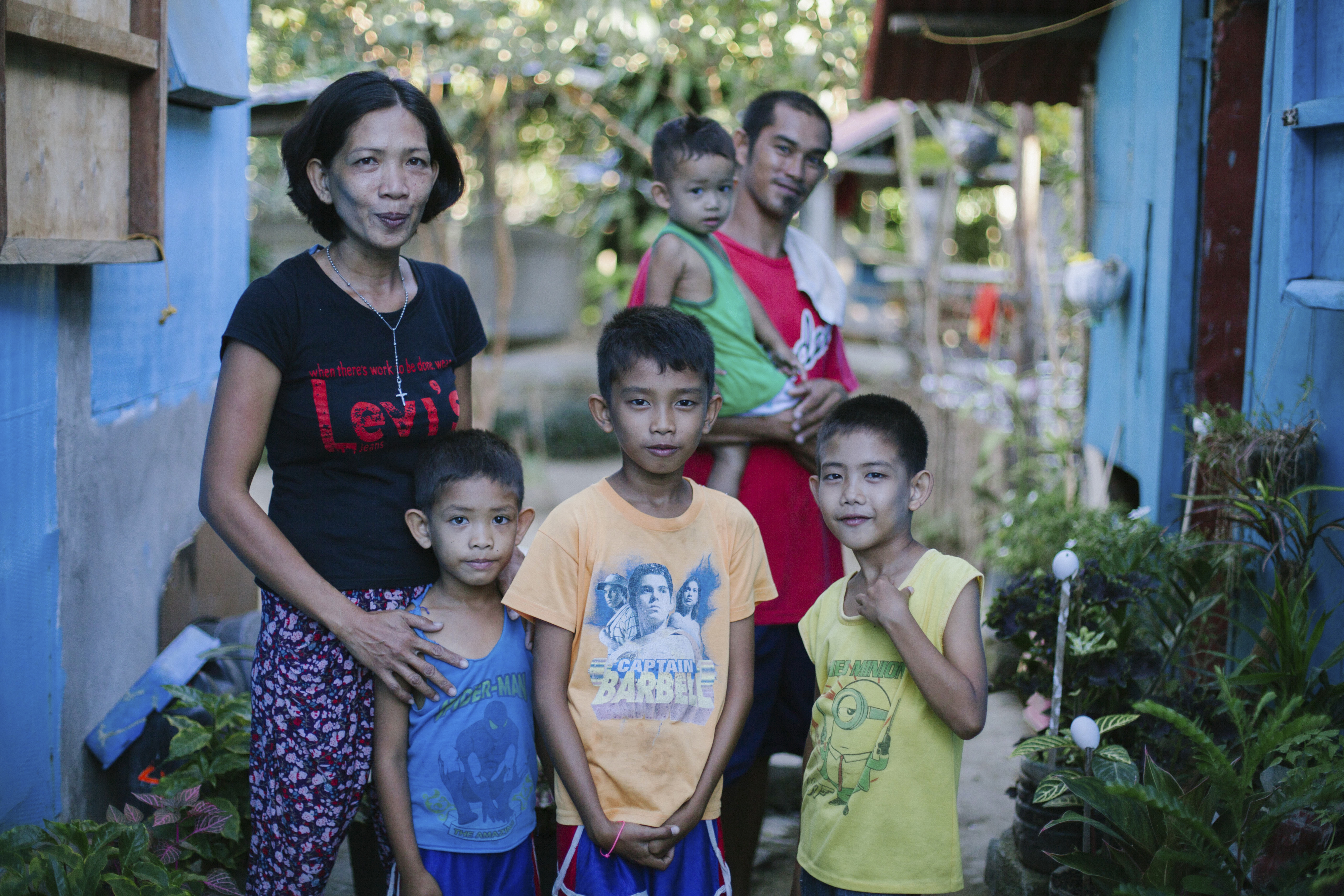 Sussett Enolva and her family stand outside their new, typhoon-resistant home in The Philippines