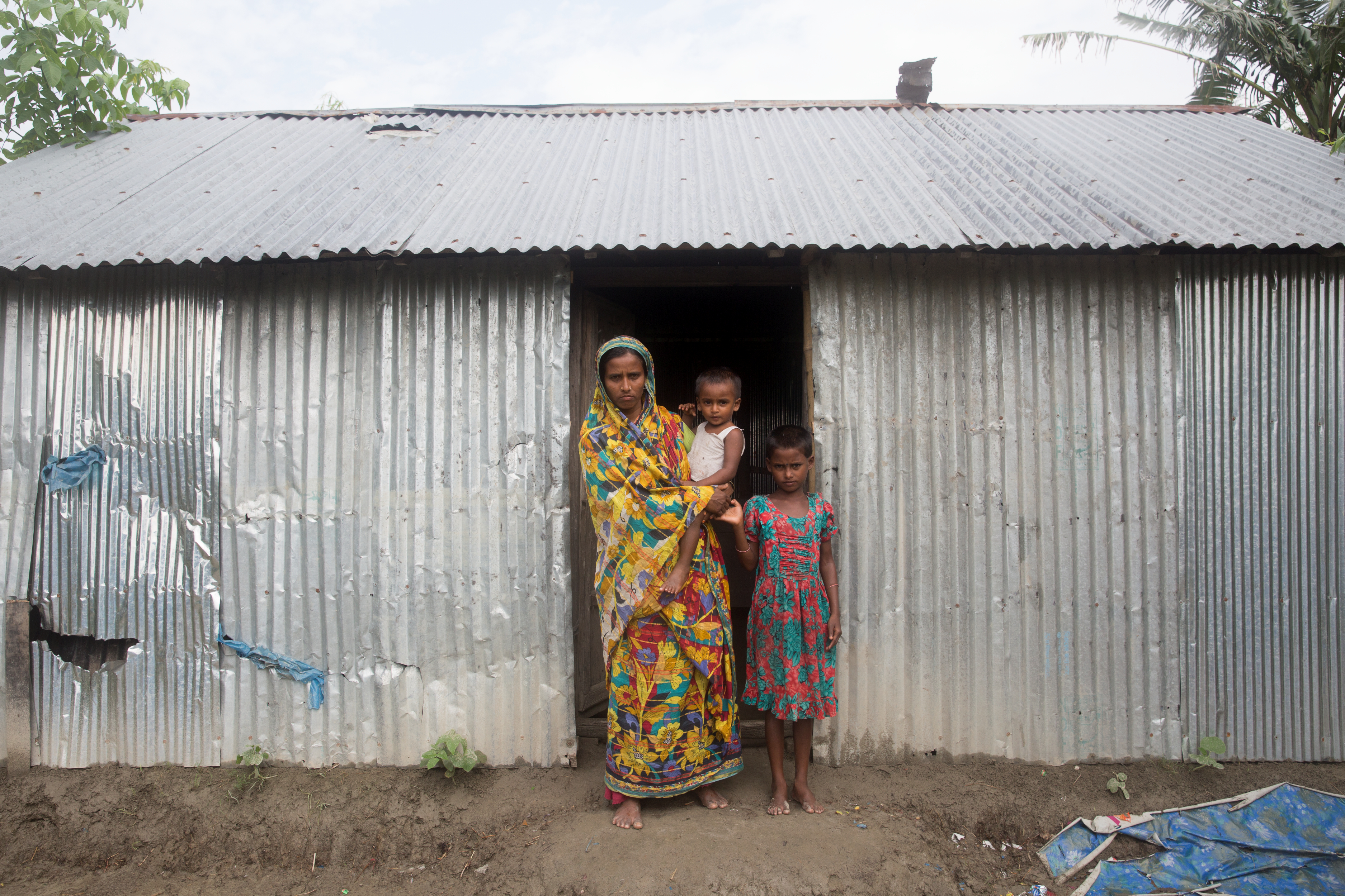 Morsheda stands in the doorway of her home with two of her children