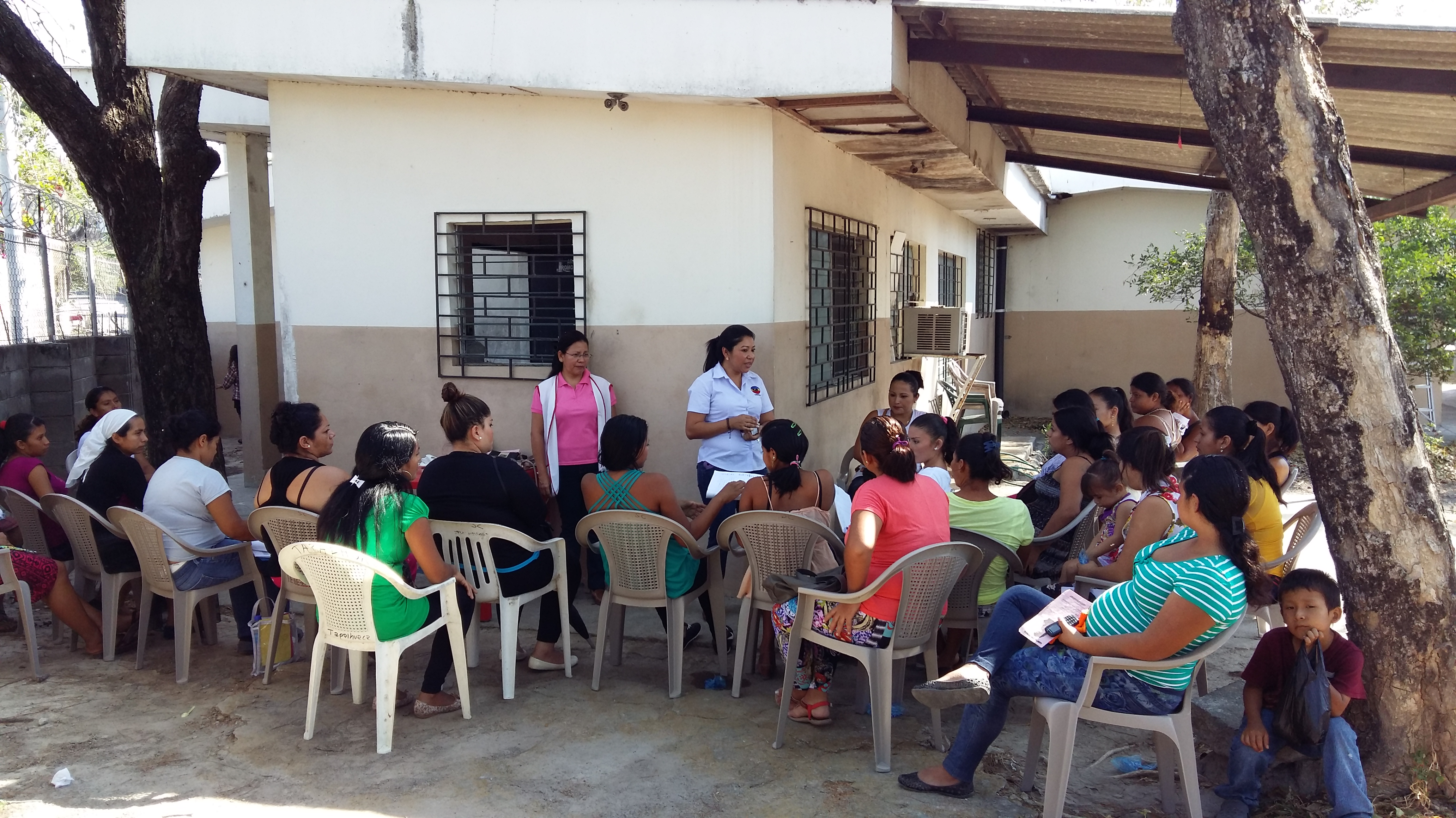 A group of women sit outside on chairs listening to a woman speak at the Mothers' Group in El Salvador
