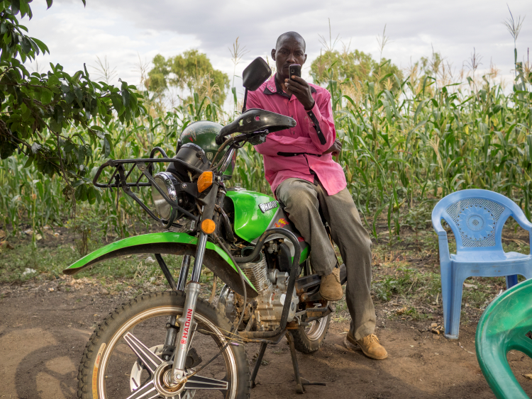 Farmer holds mobile phone in Kenya which he uses to monitor weather patterns using SMS