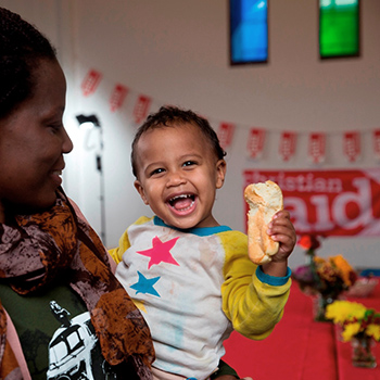 A mother holding a young boy with a bread roll in his hand, at a Big Brekkie event