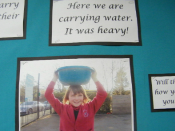 A photo of a primary school pupil carrying a bowl of water on her head