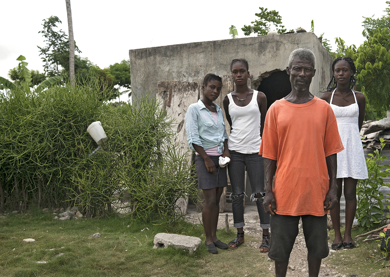 Marcelin and his daughters outside the concrete block they live in