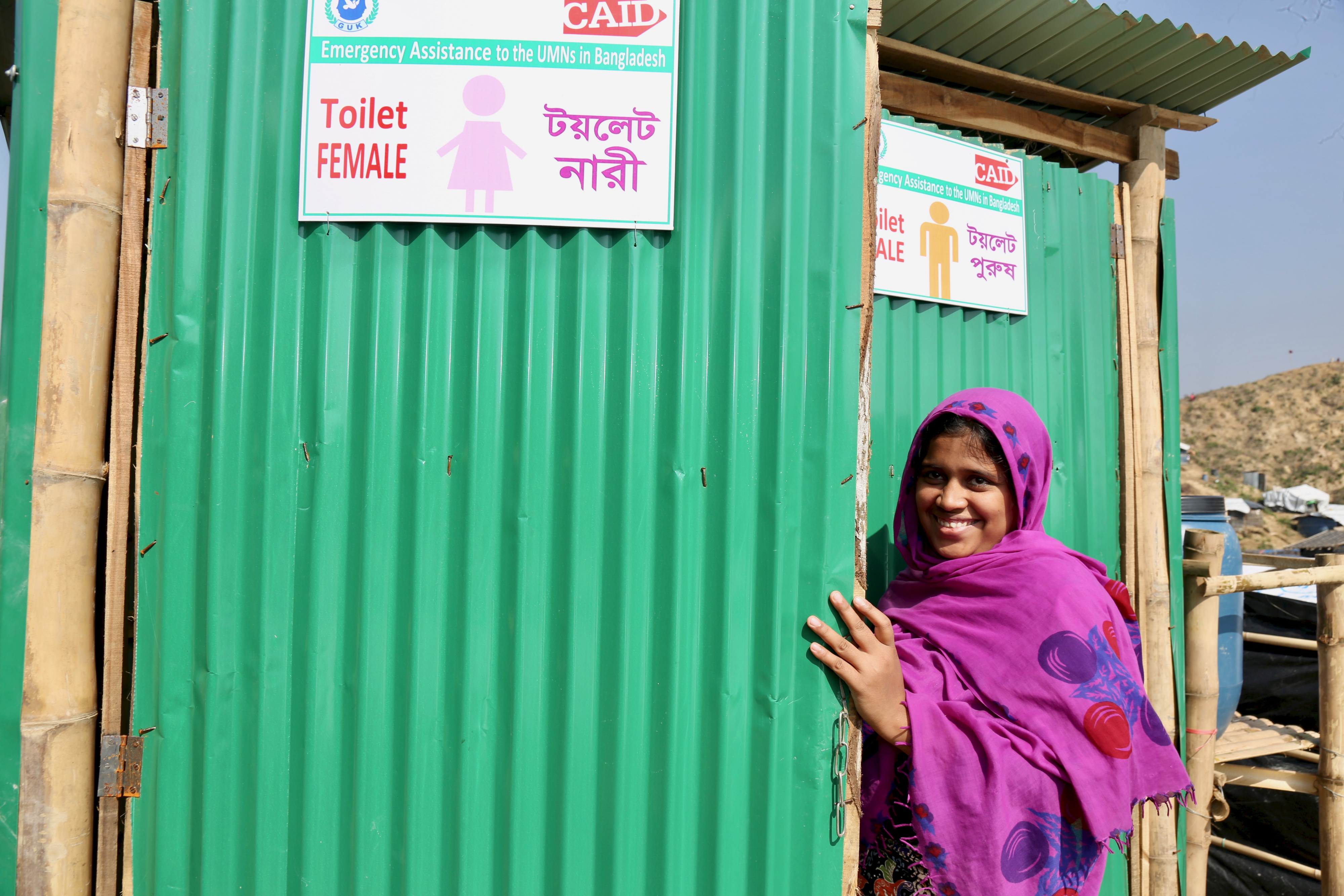 Halima Sudia stands smiling outside women's toilet in Bangladesh camp