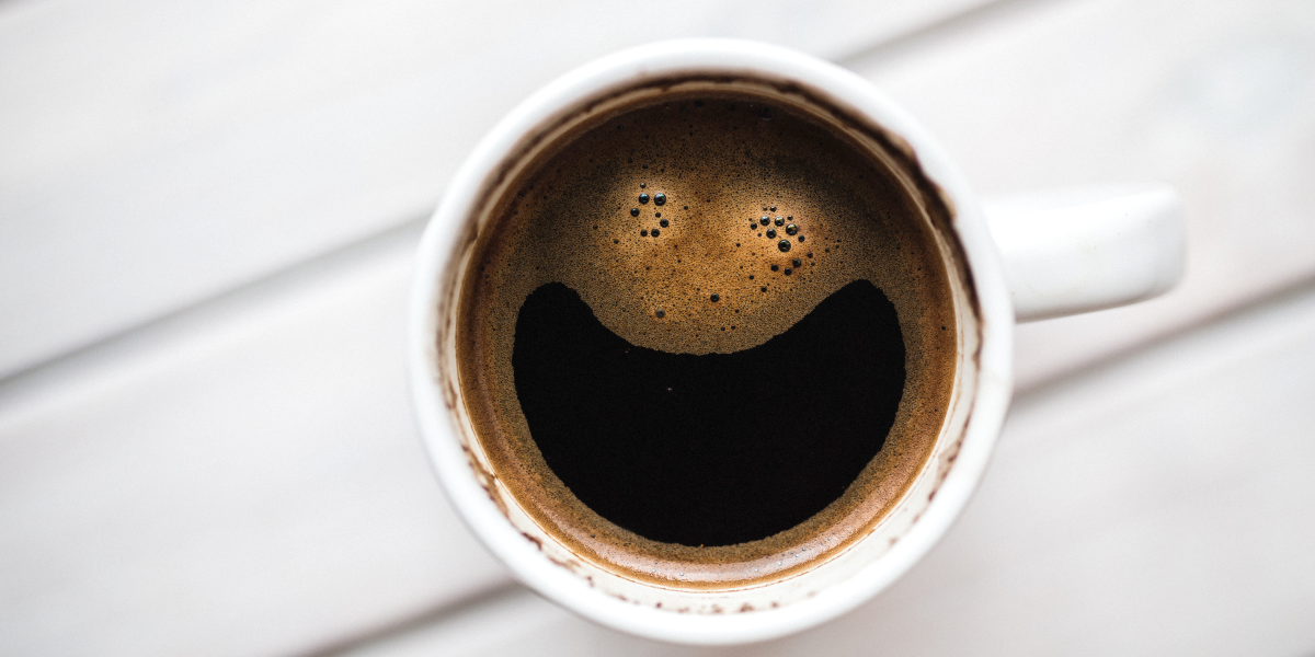 Coffee cup with froth creating a smiling face