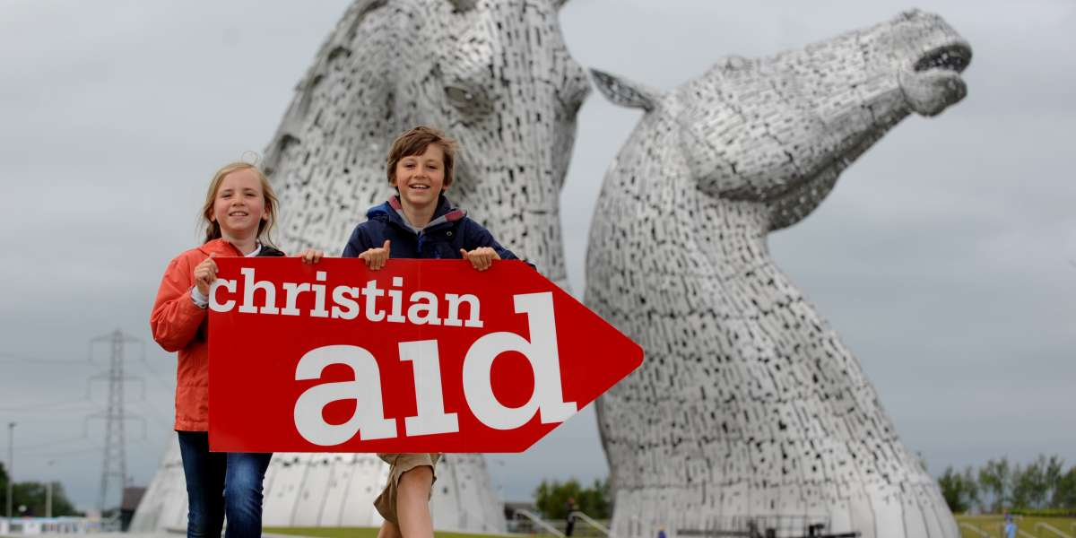 Two children holding a Christian Aid flag in front of a large horse sculpture