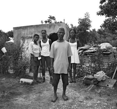 Marcelin Abellard and daughters outside their makeshift home – an abandoned concrete shower block – after their house was destroyed by Hurricane Matthew, Haiti