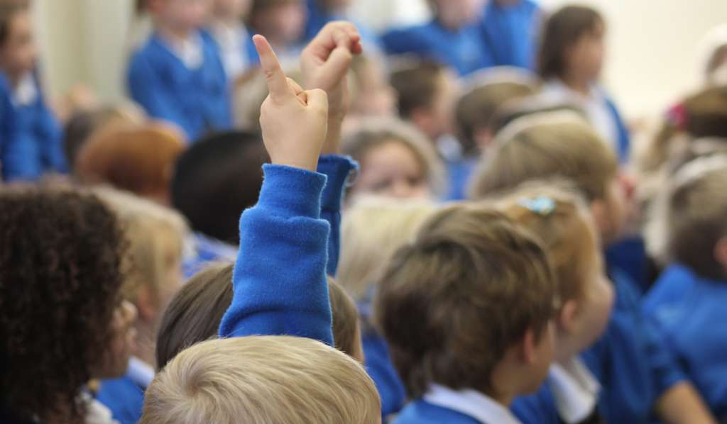 A group of primary school children with their hands up in class
