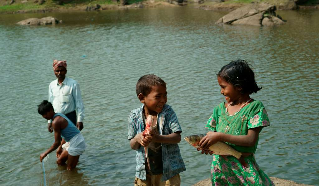 Girl and boy smiling, holding fish, with people fishing in lake in background.
