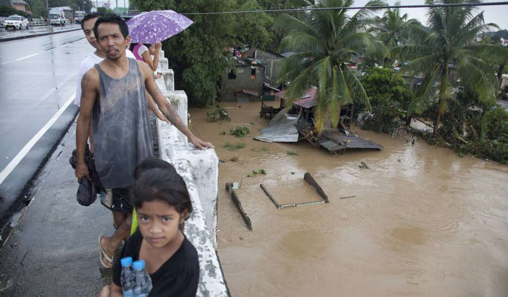 Adults and a child stand on a bridge in Metro Manilla with a flooded river flowing below