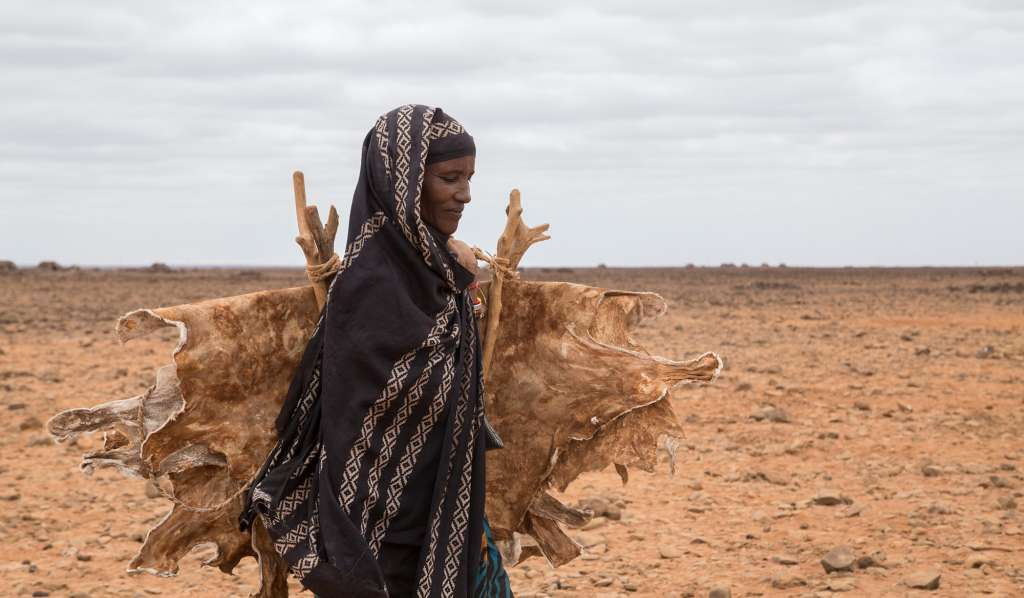 Dimma Gollo walks through dry land in northern Kenya