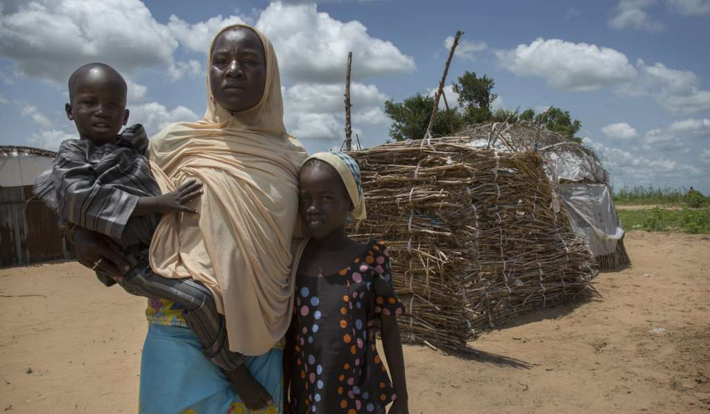 Falmata Bulama with her children, standing in front of makeshift buildings