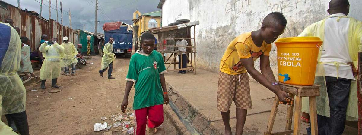 Boy in street in Sierra Leone washing his hands at wash station set up to control Ebola.
