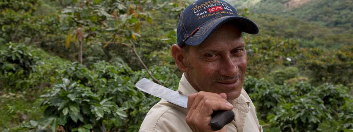 Man holding machete smiling at camera