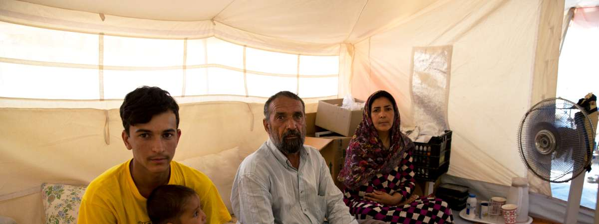 Nejebar with her husband and two sons in a tent.