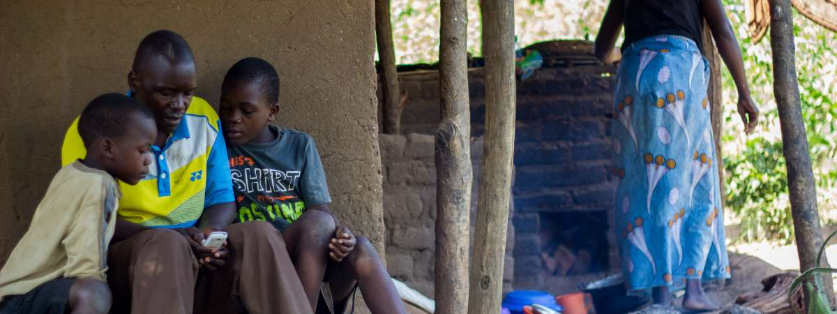 Frank is showing his children his phone outside his home in Malawi.