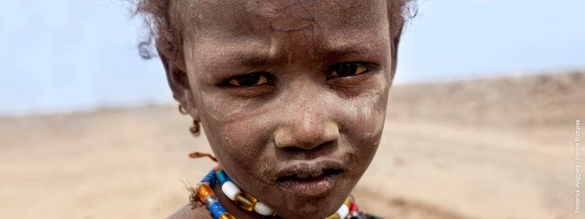 A close up of a child in front of a dry landscape