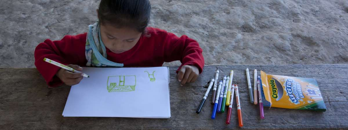 A girl drawing a picture of her home in Bolivia