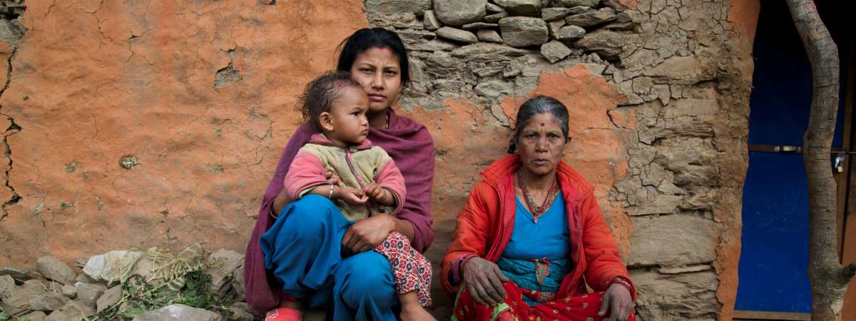 A grandmother, mother and child sit outside their collapsed home in India