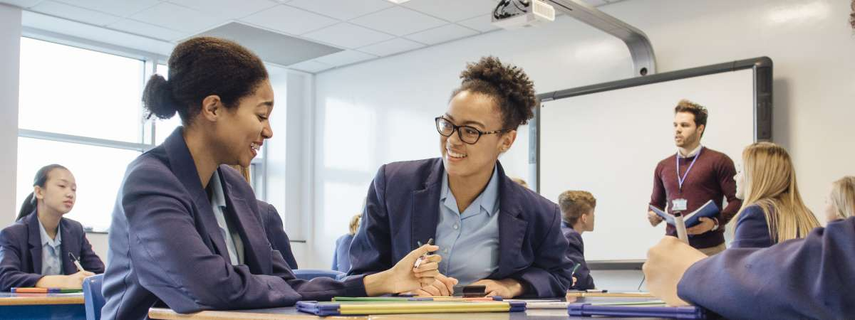 Two female secondary school pupils working together in class