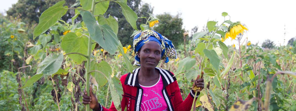 Jacqueline, a sunflower seed and vegetable farmer from Burundi, stands among long grass