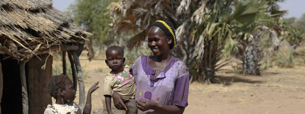 Maureen and her two children stand outside her house in Nyamlel, Aweil West, South Sudan