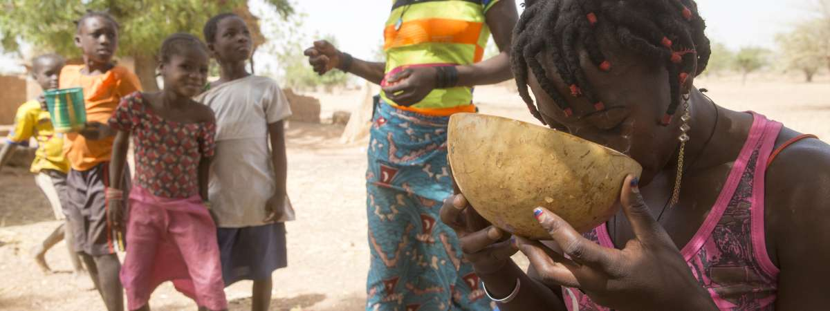 Salamata drinks from a bowl, with her children in the background.