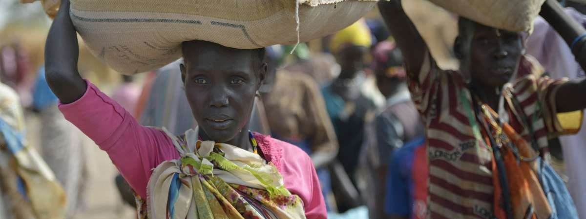Displaced women carrying food sacks, South Sudan
